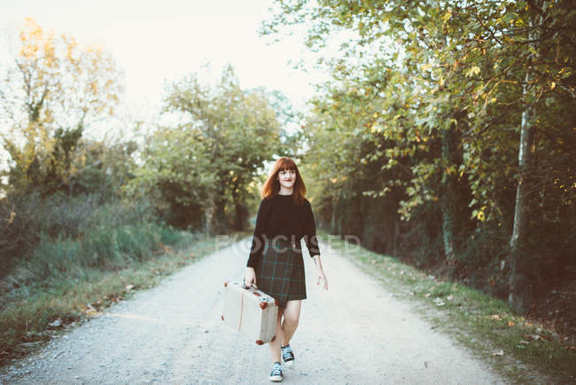 Smiling ginger girl walking with suitcase on road — Stock Photo