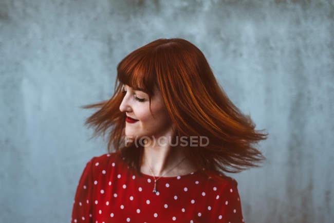 Ausdrucksstarkes rothaariges Mädchen mit wehendem Haar auf grauem Hintergrund — Stockfoto