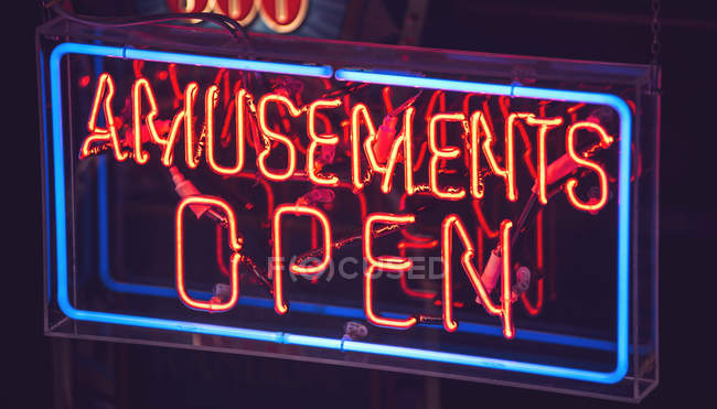 Bright neon sign with amusements open inscription — Stock Photo