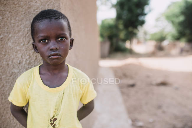 Goree, Senegal- 6 de dezembro de 2017: Retrato de criança africana inclinada na parede e olhando para a câmera ao ar livre . — Fotografia de Stock