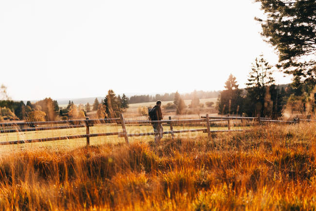 Traveler posing near rural fence at autumn countryside field — Stock Photo