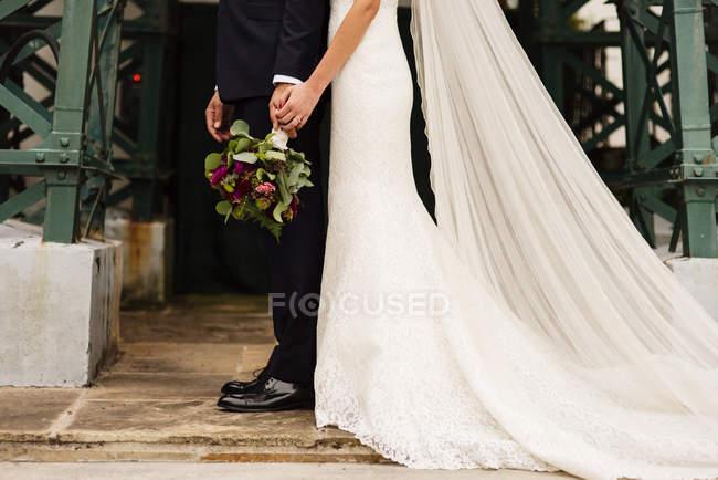 Vue de côté de récolte des mariés avec la mariée élégante posant ensemble et main dans la main — Photo de stock