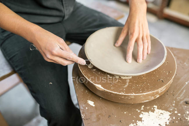 Crop potter hands shaping clay plate edge with instrument — Stock Photo