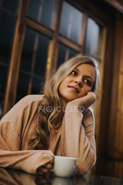 Ritratto di ragazza bionda in posa con tazza di caffè e mento in mano — Foto stock
