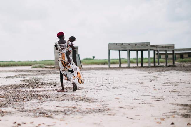 Yoff, Senegal - 06 de diciembre de 2017: vista posterior de mujer caminando y llevando el niño en las manos. - foto de stock