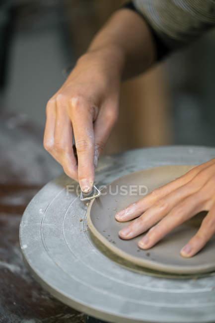 Mãos artesanais cultura esculpir borda prato de argila com instrumentos — Fotografia de Stock