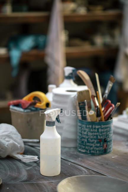 Инструменты и посуда на рабочем столе гончара в мастерской — стоковое фото