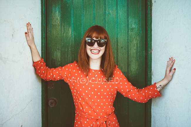 Smiling redhead girl in sunglasses posing at camera at doorway — Stock Photo