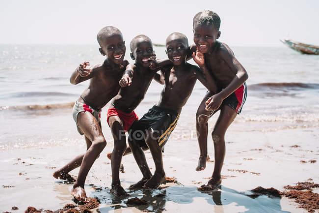 Goree, Sénégal- 6 décembre 2017 : Des garçons africains joyeux posant et s'amusant sur le rivage sablonneux au bord de la mer . — Photo de stock