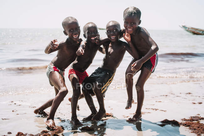 Goree, Senegal- December 6, 2017: Cheerful African boys posing and having fun on sandy shore at seaside. — Stock Photo