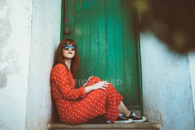 Red haired woman wearing red polka dots patterned dress posing at doorstep in doorway with green wooden door — Stock Photo