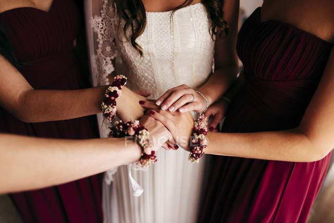 Mid section of bridesmaids holding hands together before wedding ceremony. — Stock Photo