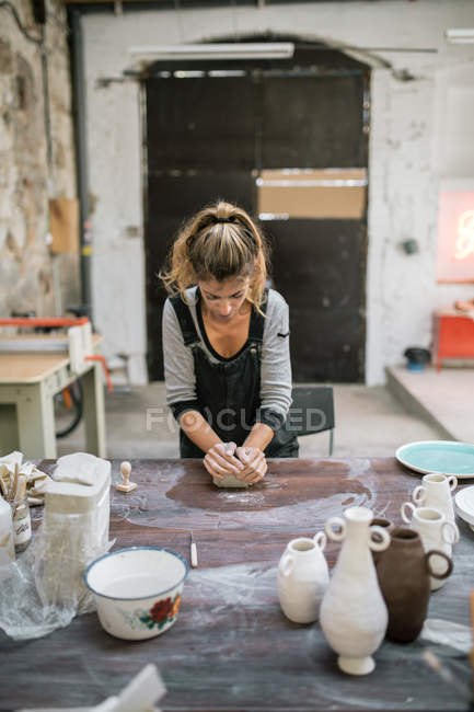 Concentrated woman kneading clay on wooden table at workshop — Stock Photo