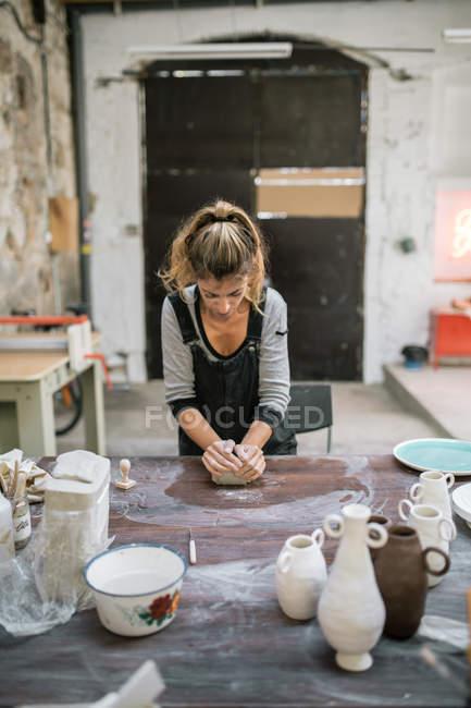 Концентрированная женщина месит глину на деревянном столе в мастерской — стоковое фото