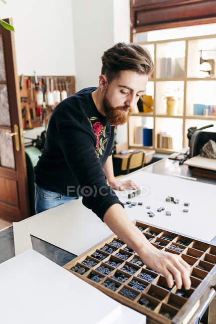 Portrait of man working in bookmaking manufacture and composing printing press letters on desktop. — Stock Photo