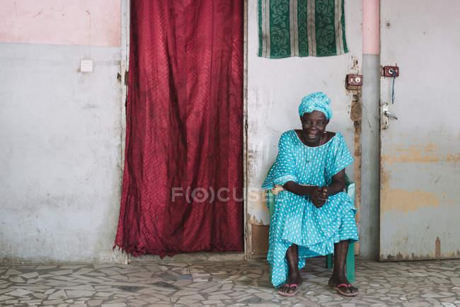 Goree, Сенегалу-6 грудня 2017: Старший жінка в синій сидить біля будинку Дорвей і дивлячись на камеру. — стокове фото
