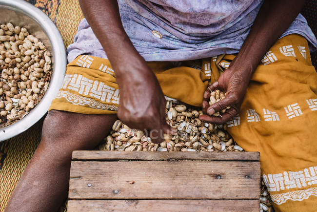 Crop shot from above of male midsection shelling roasted nuts. — Stock Photo