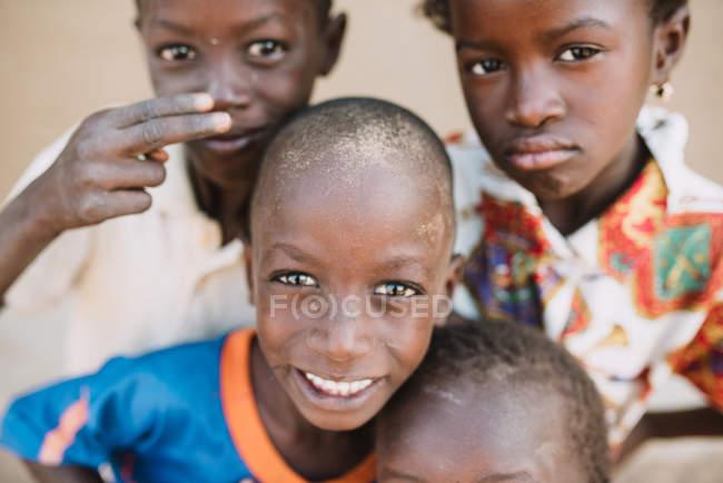 Gorée, Senegal-6 de dezembro de 2017: Retrato de crianças negras, olhando para a câmera com diferentes emoções a sorrir. — Fotografia de Stock
