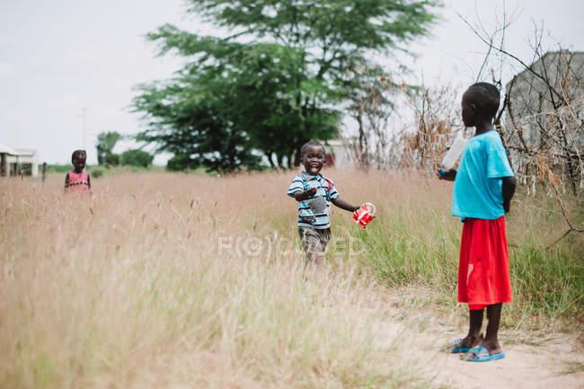 Yoff, Сенегалу - 6 грудня 2017: мало дітей ходьбі разом в траві, на Луці. — стокове фото