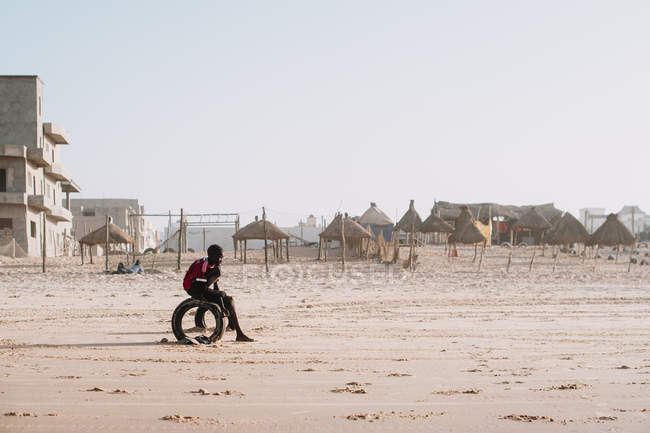 Yoff, Senegal- December 6, 2017: Side view of black kid relaxing on sandy tropical beach of ocean with straw umbrellas on background. — Stock Photo
