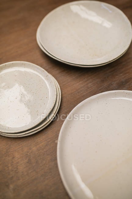 Close up view of shiny white handicraft plates on table — Stock Photo