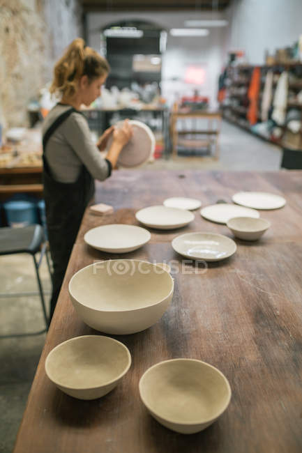 Hand maiden plates on table over potter working with clay on background — Stock Photo