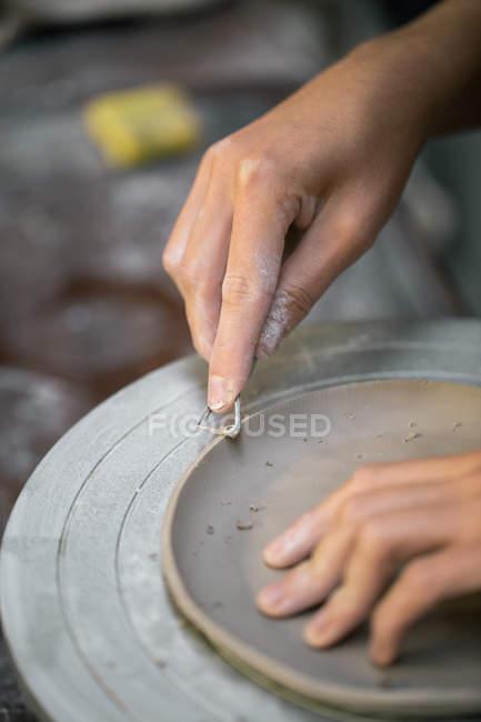 Высев женские руки гончара резьба глины края посуды с помощью инструмента — стоковое фото
