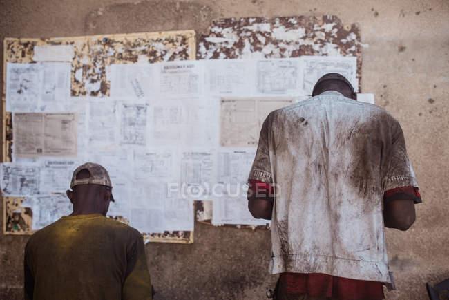 Vista traseira do africanos homens em pé perto de quadro de avisos. — Fotografia de Stock