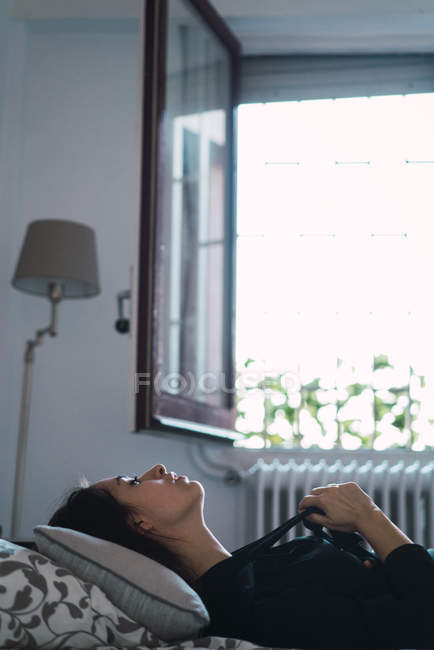 Side view of brunette woman posing in bed at home — Stock Photo