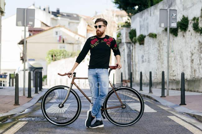 Stylish man posing with bicycle on street scene — Stock Photo