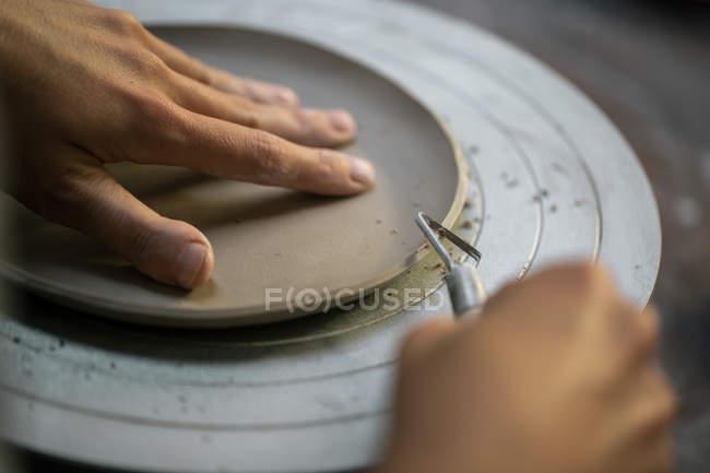 Рукоделие ремесленника, вырезающее края глиняных тарелок инструментом — стоковое фото