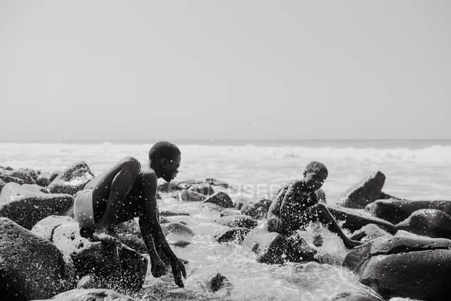 Гори, Сенегал - 6 декабря 2017 года: Веселые дети сидят на скале в брызгающейся волне — стоковое фото