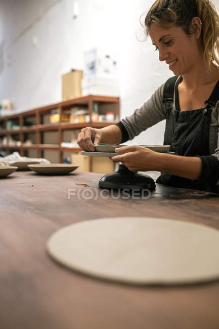 Side view of blonde woman forming plate with clay at desktop — Stock Photo