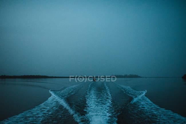 Paseos en barco por el río aguas tranquilas en la noche oscura . - foto de stock