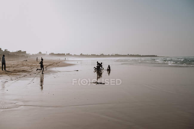 Yoff, Sénégal - le 6 décembre, 2017:Landscape de plage aux eaux calmes, sable et africaines enfants s'amuser dans l'eau de lavage — Photo de stock