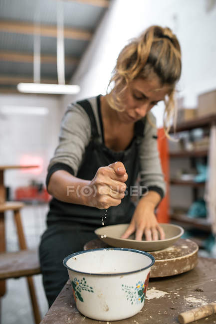 Portrait  of female potter moistening piece of clay while modelling plate at workshop — Stock Photo