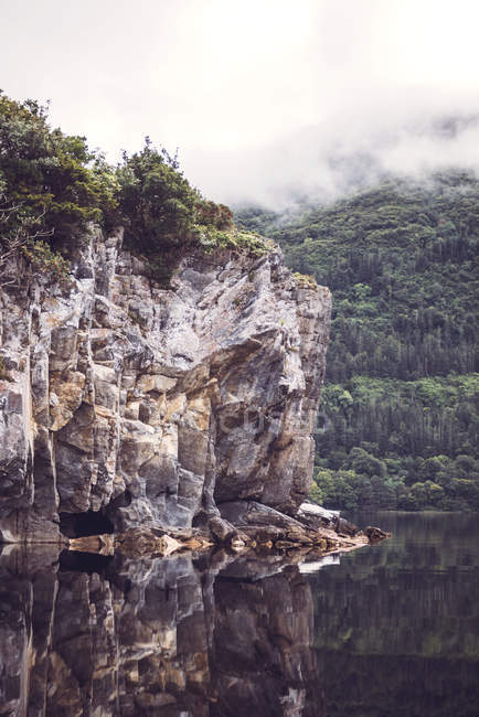 Rocky cliff over lake with trees-covered hill slope — Stock Photo