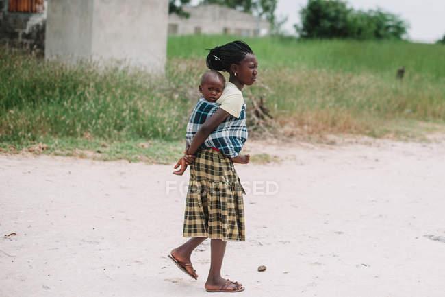 Yoff, Senegal - 06 de diciembre de 2017: vista lateral de mujer negro caminando en el camino y llevando a niños pequeños en espalda. - foto de stock