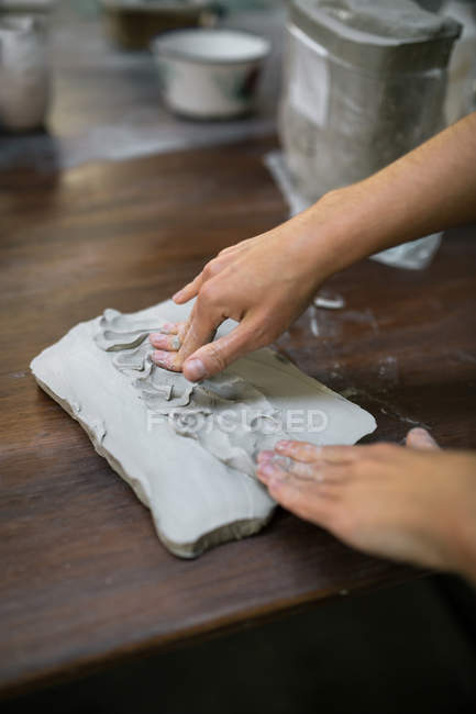 Crop image of female hands kneading clay piece on table — Stock Photo