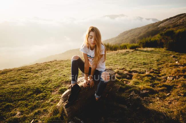 Молодая женщина сидит на камне — стоковое фото