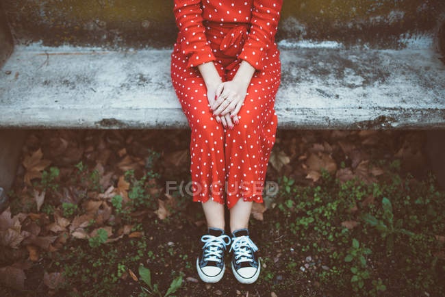 Crop female wearing red polka dots dress sitting on mossy stone bench — Stock Photo