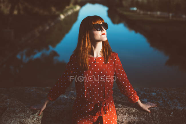 Young redhead woman in red clothing and sunglasses posing confidently in sunlight over lake. — Stock Photo