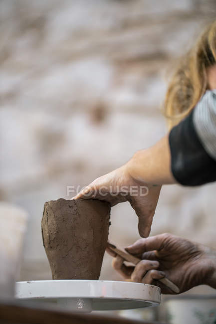 Crop of female potter making pot with clay — Stock Photo
