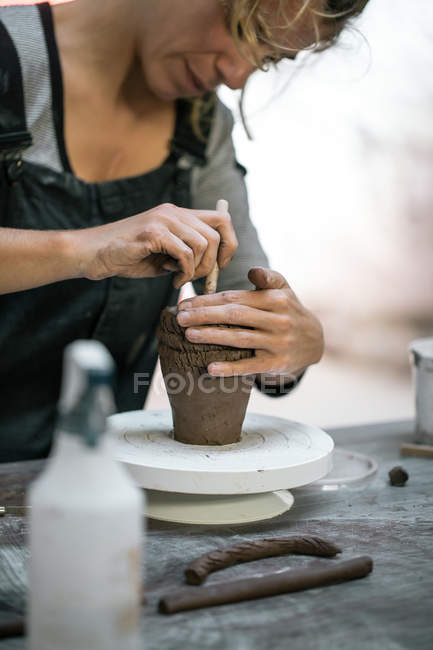 Mid section of woman making pot at table in workshop — Stock Photo