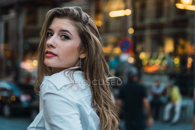 Portrait of brunette girl walking at street scene and looking over shoulder at camera — Stock Photo