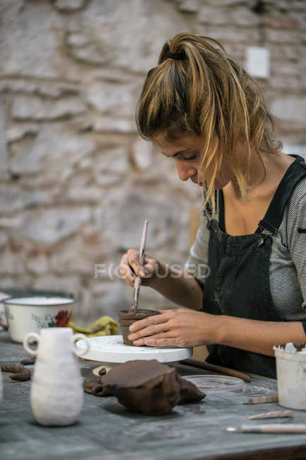Side view of  woman working with clay at workshop — Stock Photo