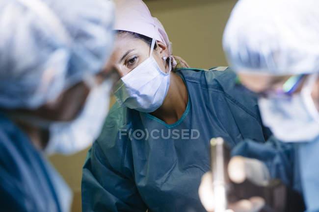 Porträt einer Frau mit Maske, die Ärzten bei Operationen im Krankenhaus zusieht — Stockfoto
