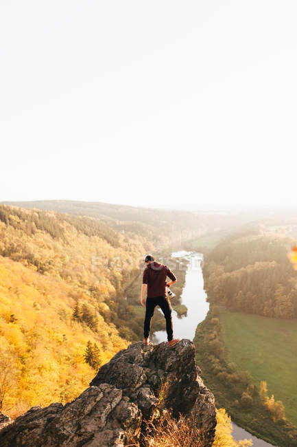 Back view of man posing on rocky cliff above picturesque valley with river on backdrop. — Stock Photo