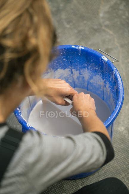Over shoulder view of potter working with liquid clay in busket — Stock Photo