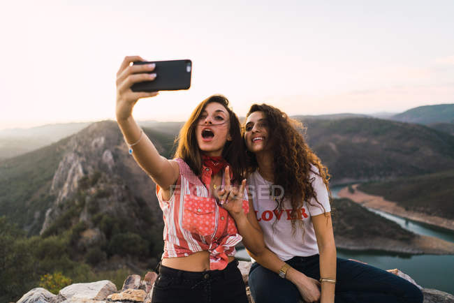 Zwei junge Mädchen posieren für Selfie auf Hintergrund der Berge in der Sonne — Stockfoto